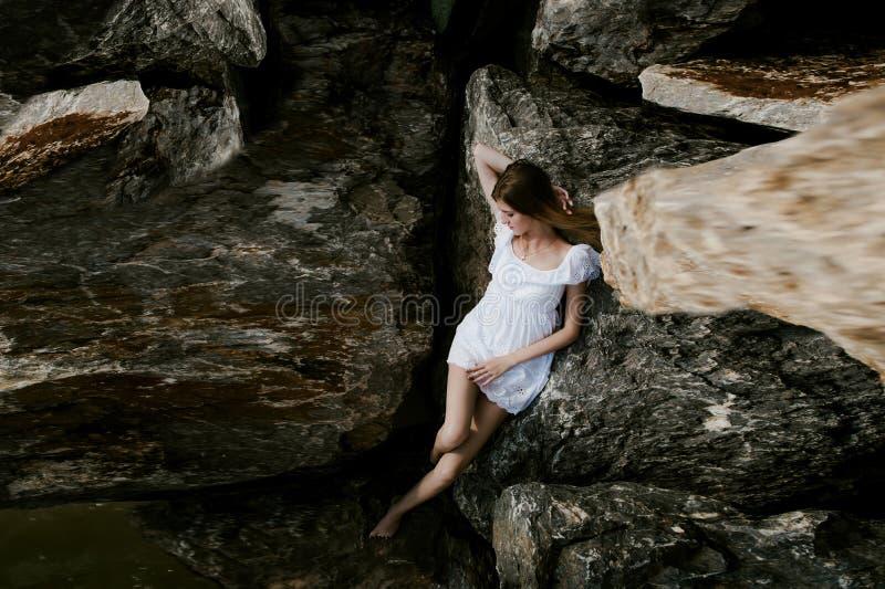 苗条少妇画象石头的在海附近 免版税图库摄影