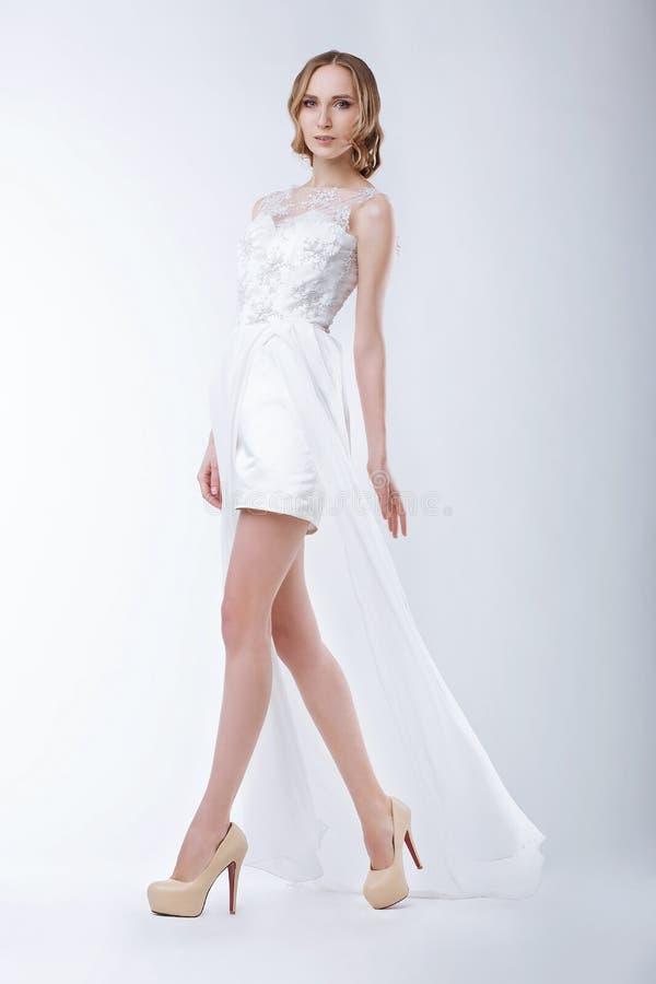 苗条时装模特儿佩带的白色礼服 免版税库存照片