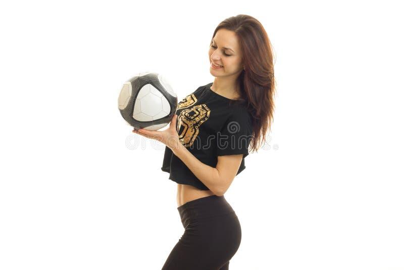 苗条年轻运动员在有球的演播室站立在手和微笑上 免版税库存照片