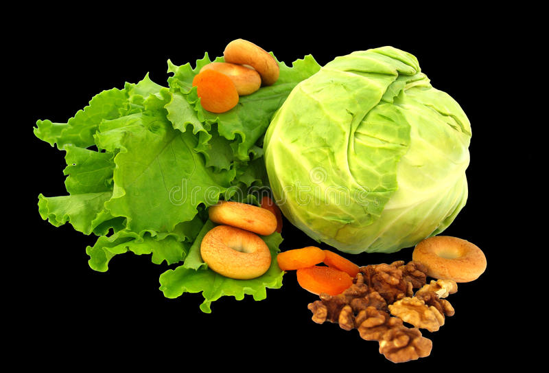 莴苣、圆白菜、干果、苹果,干燥,胡说和杏干静物画在黑背景隔绝的 库存图片