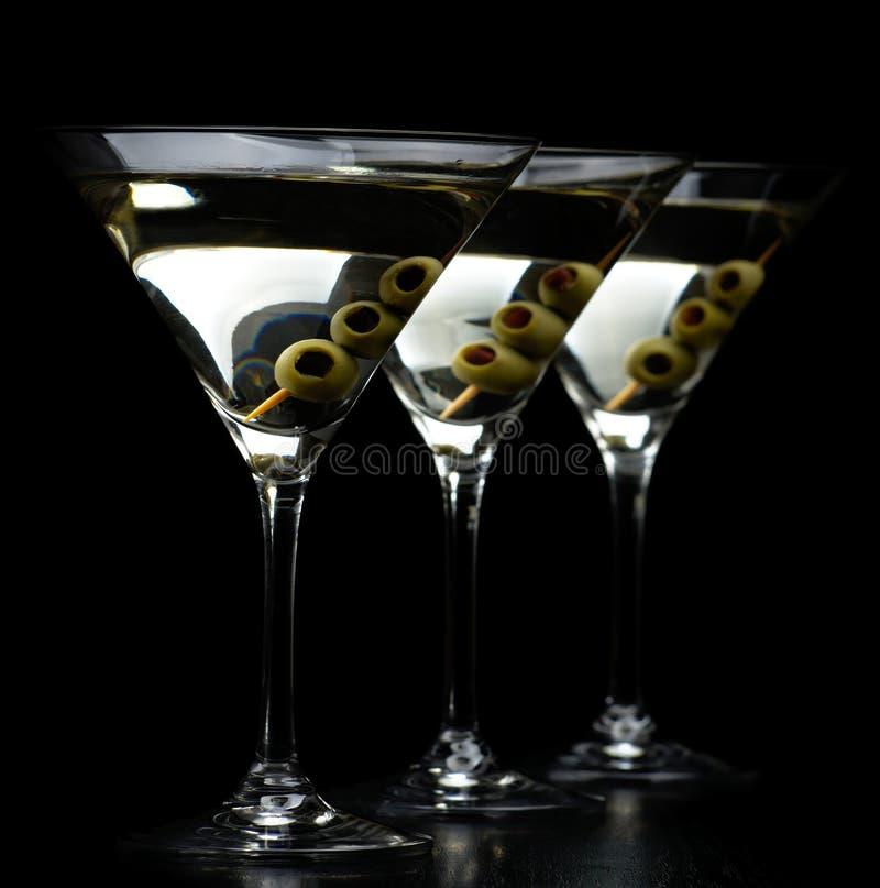 苦艾酒马蒂尼鸡尾酒饮料用在黑色隔绝的橄榄 库存图片