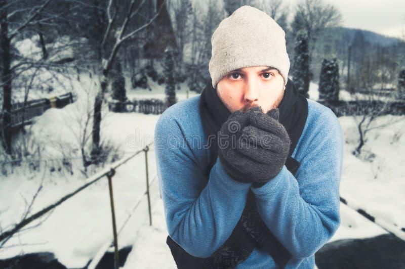 英俊人坐外部和结冰 免版税库存图片