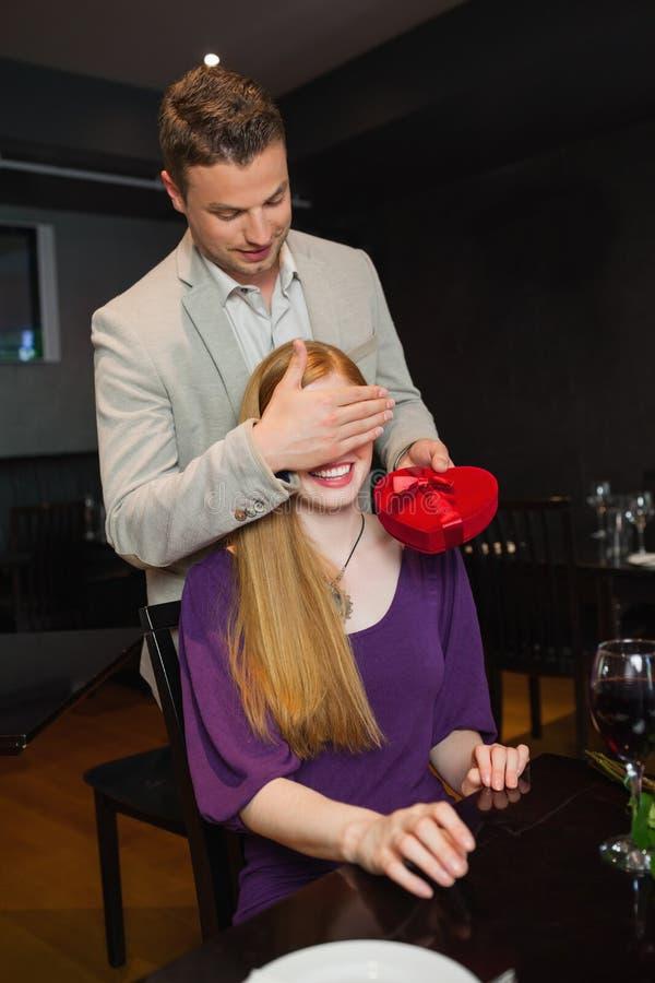 英俊人提供当前为他微笑的女朋友 免版税库存图片