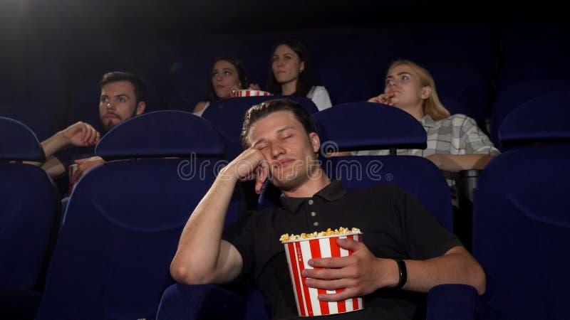 英俊人睡着在电影期间在戏院 库存照片