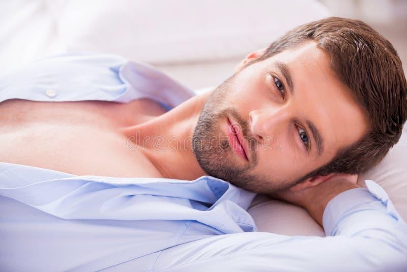英俊在床上 免版税图库摄影