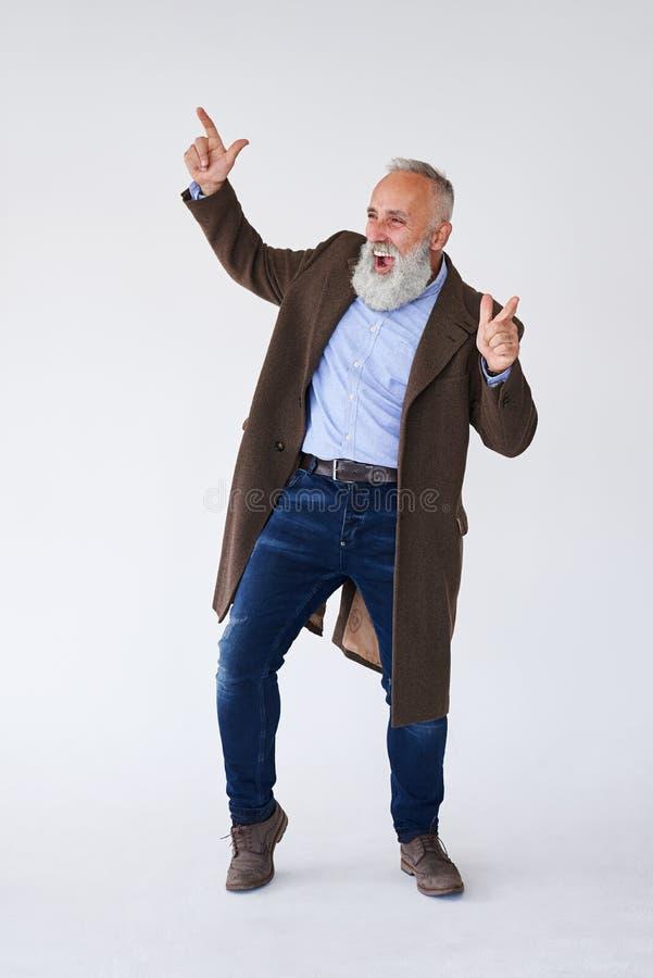 英俊成熟有胡子在举手的外套在演播室 库存图片