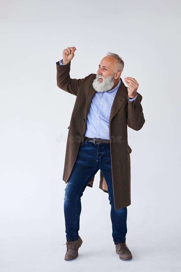 英俊成熟有胡子在外套获得乐趣在演播室 库存图片