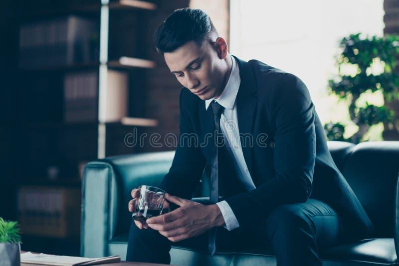 英俊旁边的简历照片的关闭他他他沉思考虑手胳膊威士忌酒饮料眼睛闭上享受正式的穿戴 库存图片