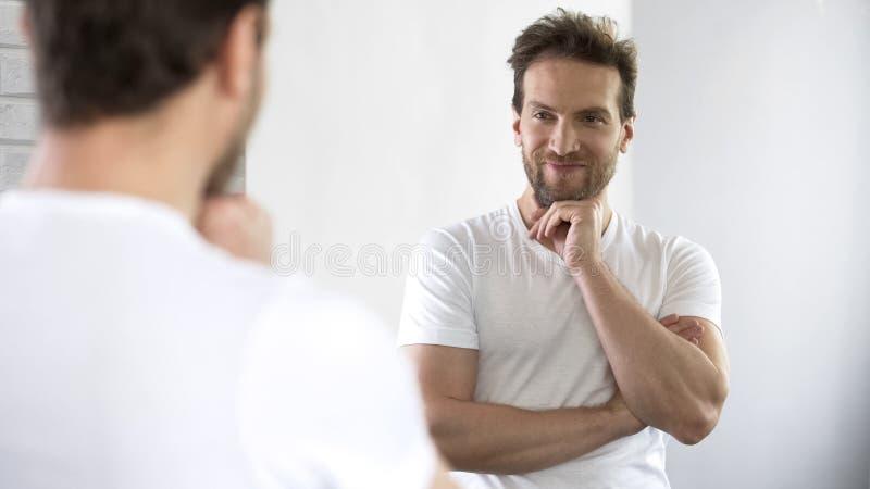 英俊男性摆在镜子,感到愉快和快乐,对生活满意 库存图片