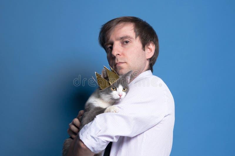 英俊的严肃的人侧视图有灰色猫的 库存图片