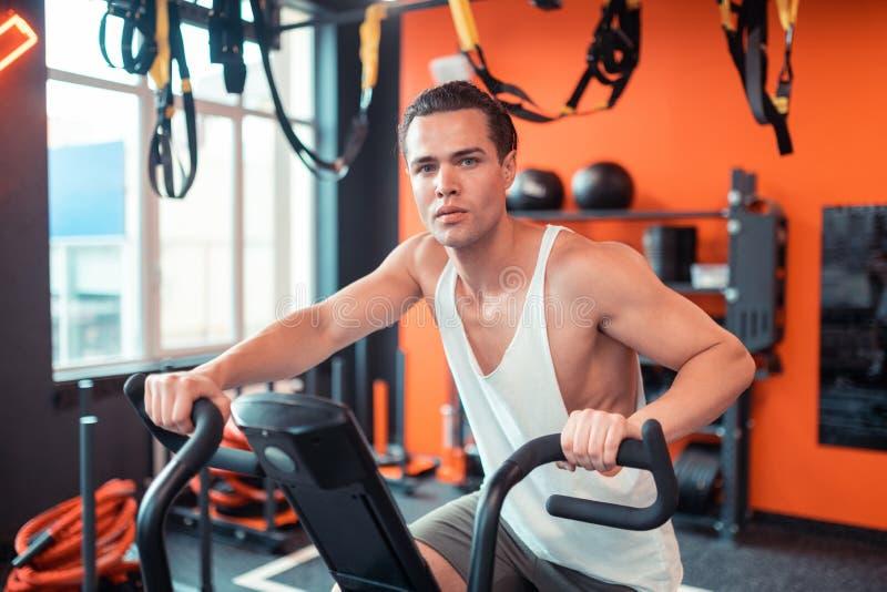 英俊的严肃的人坐体育机器 免版税库存照片
