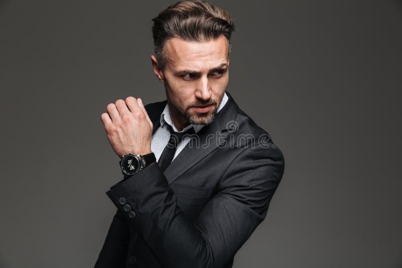英俊的严肃的商人画象在看a的黑衣服的 免版税库存照片