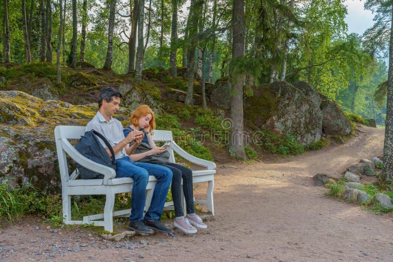 英俊的中年人和年轻俏丽的夫人坐长凳 免版税库存照片