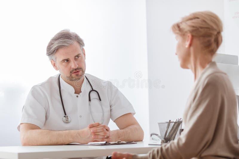 英俊的中年医生和女性患者在医院办公室 免版税库存照片