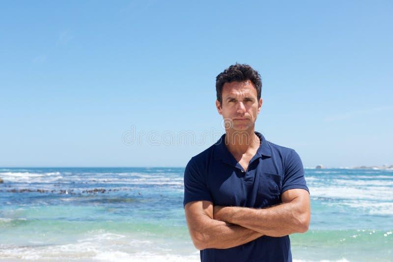 英俊的中部变老了有严肃的表示的人在海滩 免版税库存照片