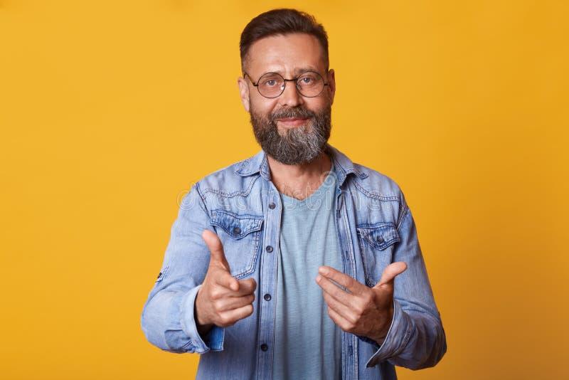 英俊的中部接近的画象变老了把手指指向的有胡子的人在黄色演播室背景隔绝的照相机,看 免版税图库摄影