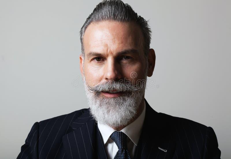英俊的中部画象变老了穿着在空的灰色背景的有胡子的绅士时髦衣服 演播室射击,事务 免版税图库摄影