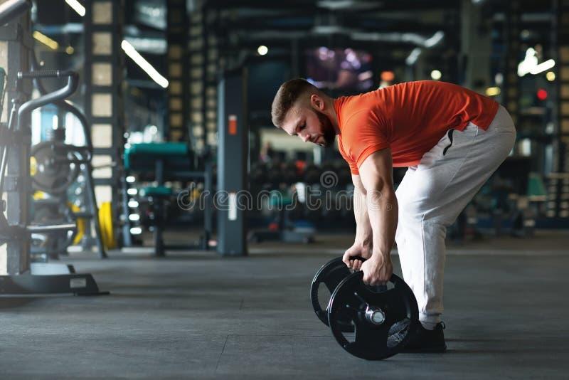 英俊的举重运动员为训练在健身房做准备 库存图片