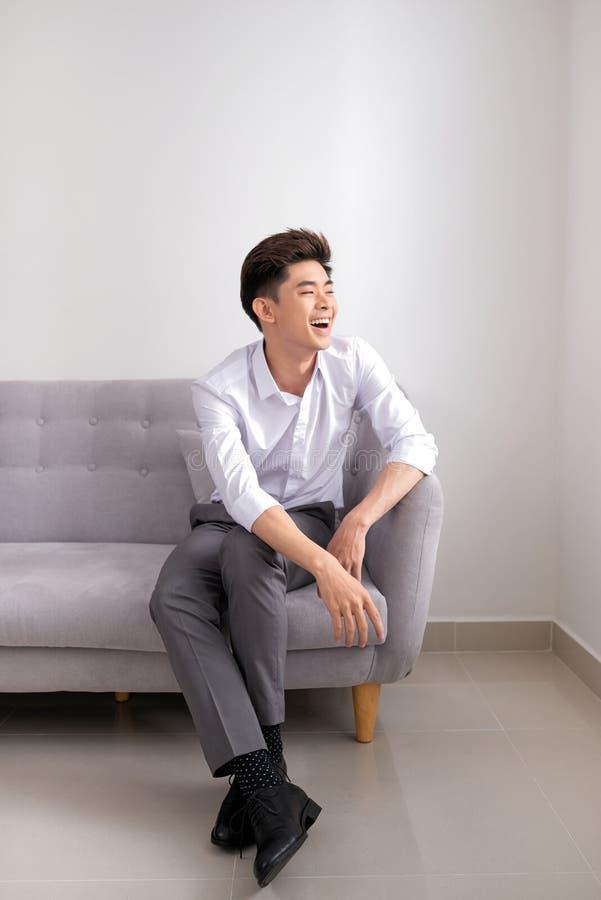 英俊的亚裔人在家坐沙发,微笑愉快 免版税图库摄影