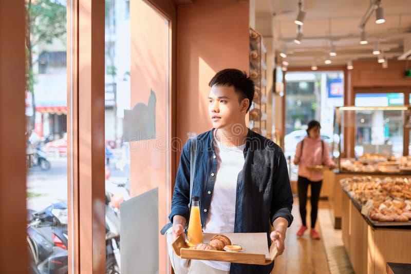 英俊的亚裔咖啡休息的人买的面包店在afterno 图库摄影