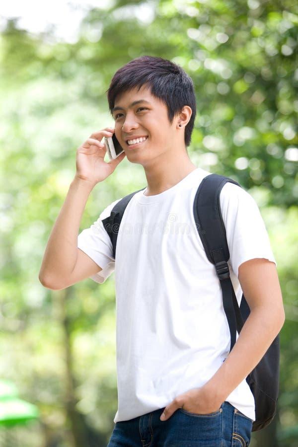 年轻英俊的亚裔学生谈话在手机 免版税库存图片