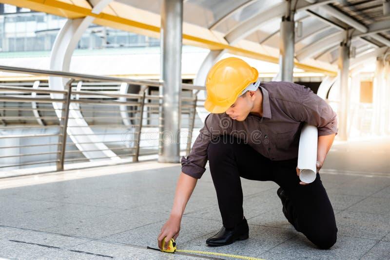 英俊的亚裔工作者或工程师人测量地板  免版税图库摄影