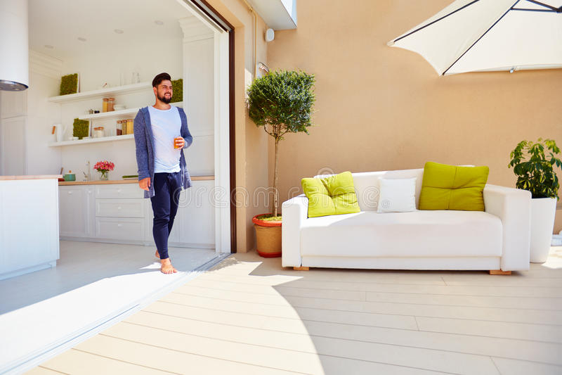 英俊的人享有在屋顶大阳台的生活,与露天场所厨房和滚滑门 库存照片