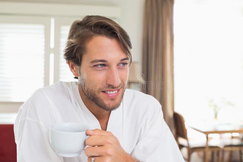 英俊的人吃早餐在他的浴巾饮用的咖啡 免版税库存图片
