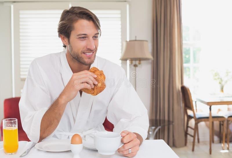英俊的人吃早餐在他的浴巾 免版税库存图片