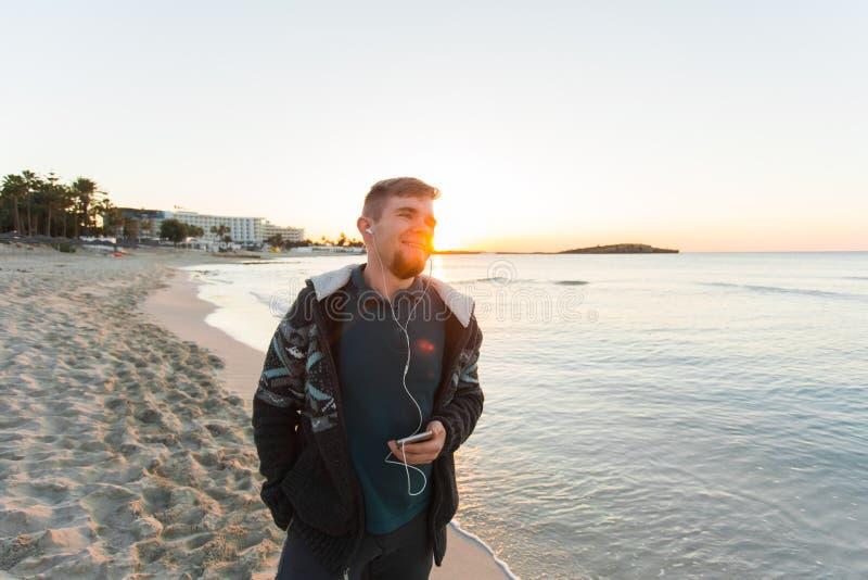 英俊的人听到在海滩的音乐 假期、旅行、技术和人概念 免版税库存图片