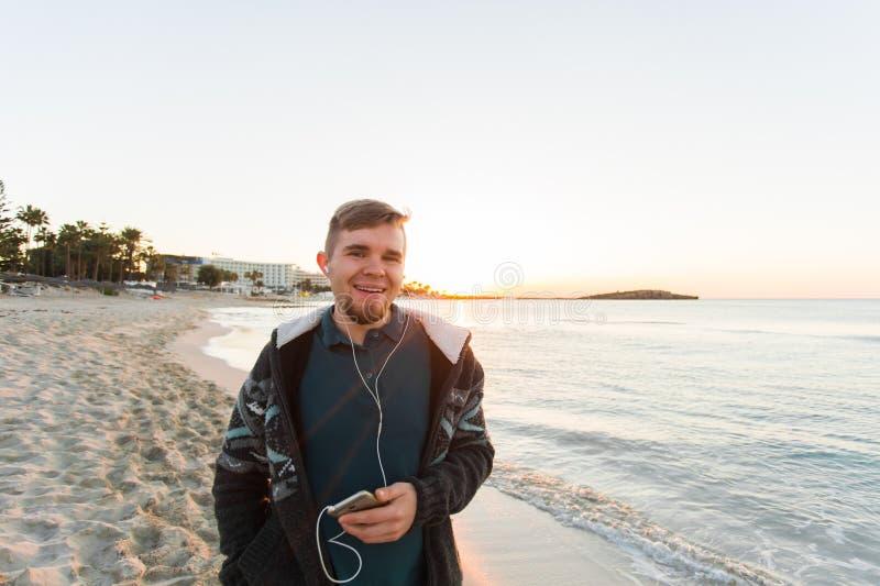 英俊的人听到在海滩的音乐 假期、旅行、技术和人概念 库存图片