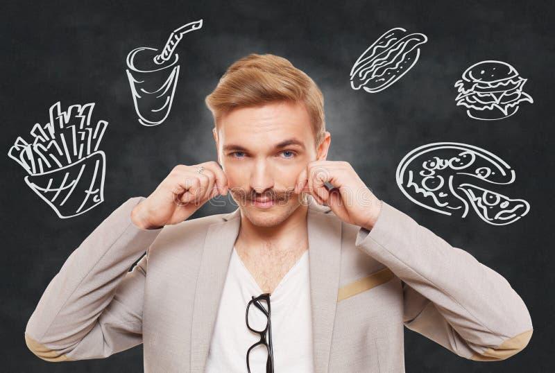 英俊的人和快餐诱惑 免版税库存照片