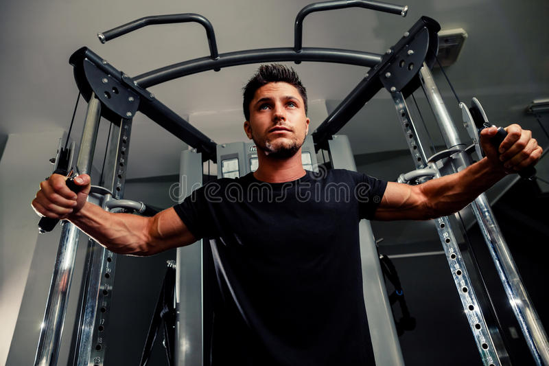 英俊的人在教练员的健身房解决 库存图片