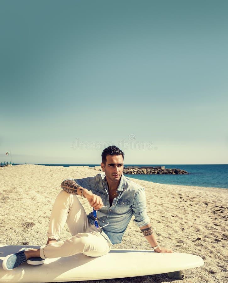 英俊的人坐冲浪板在海滩 库存照片