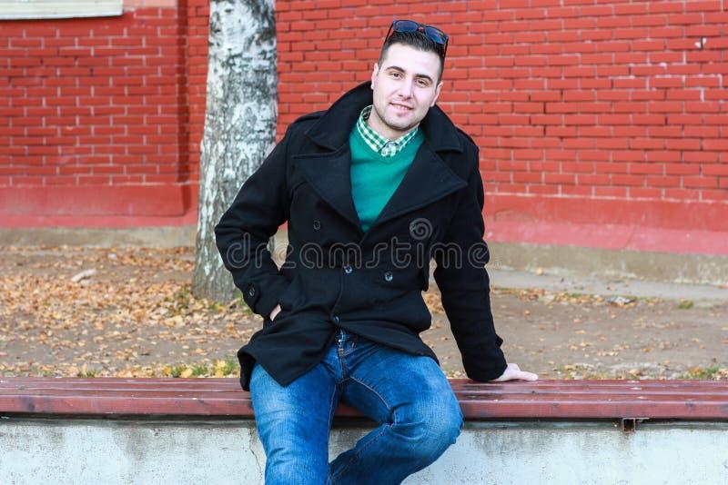 年轻英俊的人坐在一黑外套佩带的长凳 免版税库存照片