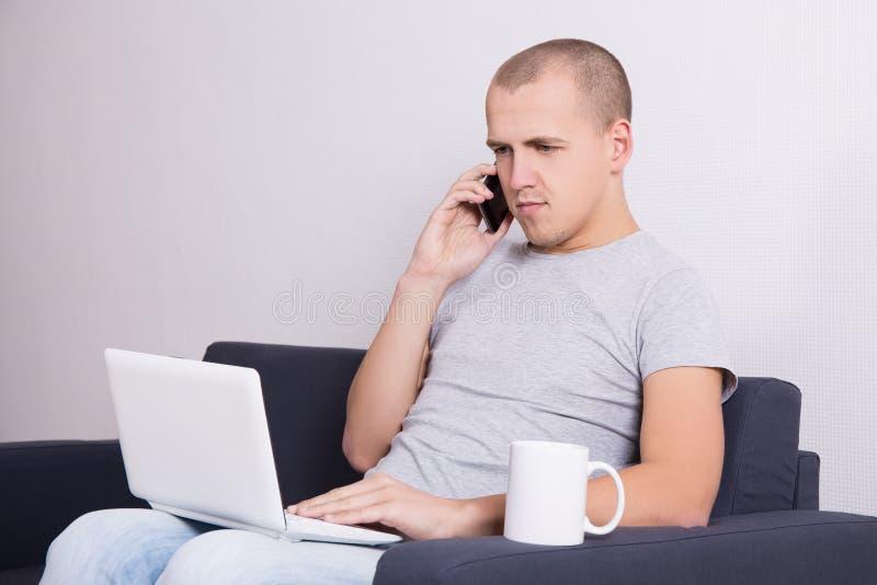 年轻英俊的人坐有计算机、电话和杯子的沙发 免版税库存照片