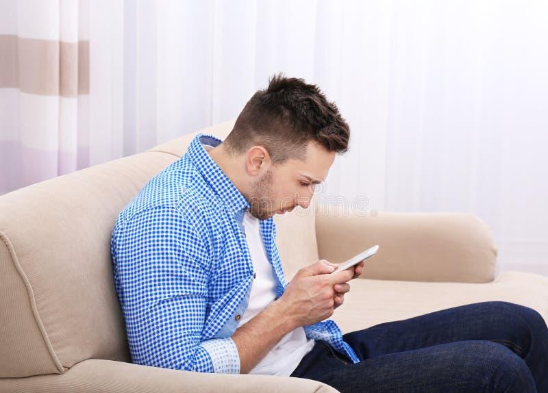 英俊的人坐的沙发年轻人 不正确姿势概念 免版税库存图片