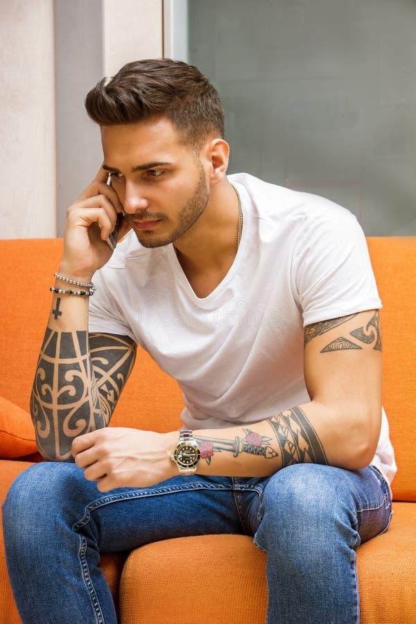 英俊的人坐长沙发谈话在电话 图库摄影