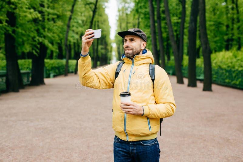 英俊的人室外画象有穿黄色滑雪衫和牛仔裤的厚实的胡子的拿着做s的背包、咖啡和智能手机 免版税库存照片
