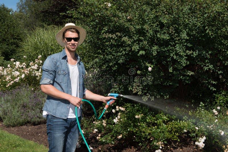 年轻英俊的人浇灌植物 免版税库存图片