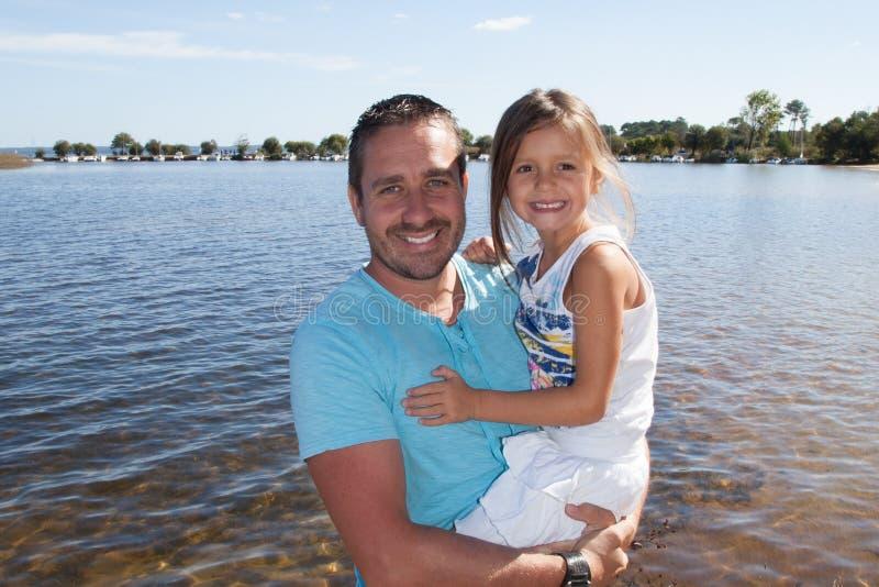 英俊的人父亲在与唯一女儿女孩的海滩假期在海边 免版税库存图片