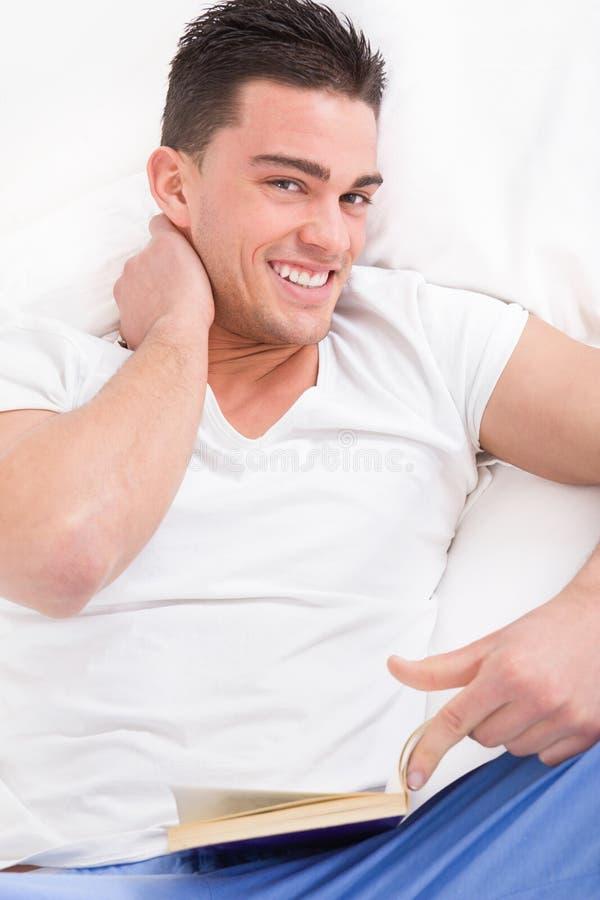 英俊的人特写镜头画象在床上充满脖子痛 库存图片