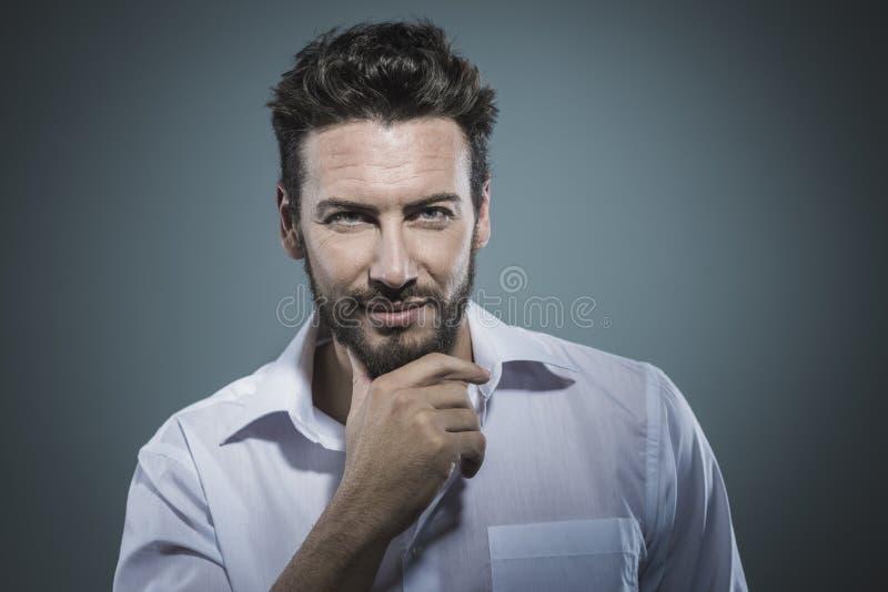 英俊的人用在下巴的手 库存图片