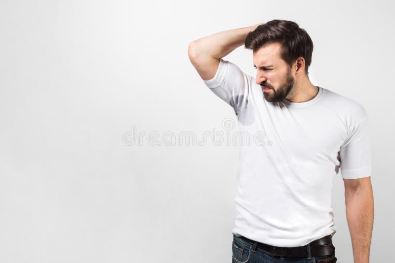 英俊的人的图片嗅他的腋窝 有一个大汗水斑点和人doesn `象的t和 免版税图库摄影