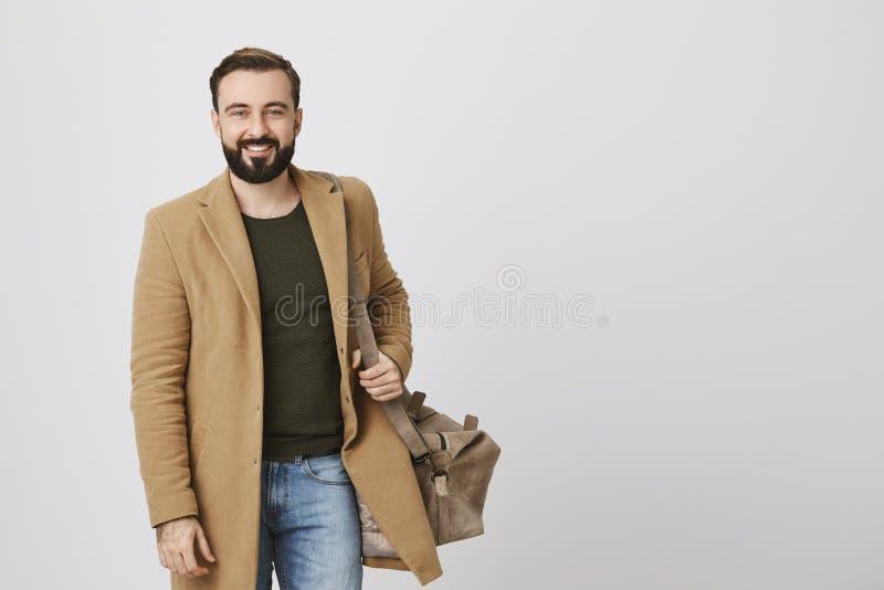 英俊的人的图片微笑对照相机的穿便衣和在白色背景的一个袋子 商人步行 库存照片