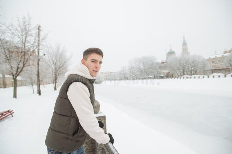 年轻英俊的人的室外冬天画象 他的摆在城市街道上的夹克和背心的, f背景美丽的少年  库存照片
