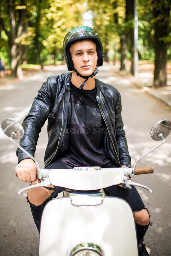 英俊的人看照相机并且微笑着,当坐他的滑行车时 库存照片