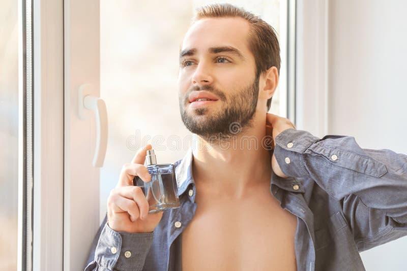 英俊的人被解扣的衬衣的和有瓶的 免版税图库摄影