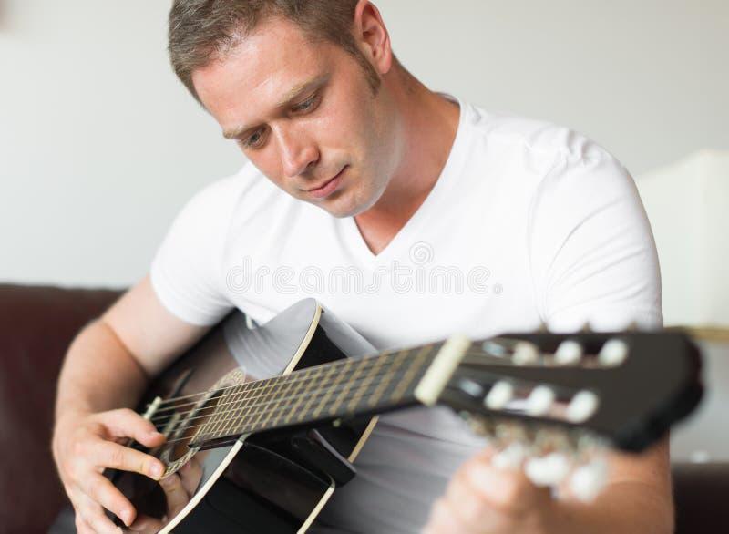 英俊的人调整的吉他 免版税图库摄影