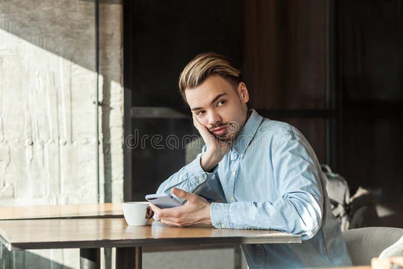 英俊的体贴的有胡子的年轻人画象坐在咖啡馆和饮用的咖啡的蓝色牛仔布衬衣的,疲乏为等待 库存图片